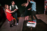 A man celebrates his birthday with a cake topped with the Syrian flag, during a Saturday night meeting of several Latin dance groups, at the Omayad Hotel, in Damascus, Syria.