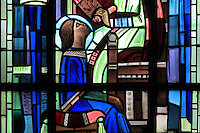 Detail of Saint Louis as a boy from the Education of Saint Louis by his mother Blanche of Castile, stained glass window, 1939, by Hollart and Provenzano, surrounding the baptismal fonts in the Chapelle Saint Louis in the Collegiale Notre-Dame de Poissy, a catholic parish church founded c. 1016 by Robert the Pious and rebuilt 1130-60 in late Romanesque and early Gothic styles, in Poissy, Yvelines, France. The chapel windows illustrate the baptism, education and coronation of Saint Louis, or King Louis IX of France, born in Poissy in 1214. The Collegiate Church of Our Lady of Poissy was listed as a Historic Monument in 1840. Picture by Manuel Cohen