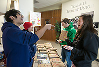 Tarun Eisen (left) of Rogers, a student in Sigma Kappa Delta English Honor Society, jokes with Sophie Horan, a student from Fayetteville, as she selects a book Thursday, Feb. 13, 2020, during the Student Ambassador and Government Association's Valentine's Cookie Day at Northwest Arkansas Community College in Bentonville. Sigma Kappa Delta offered a 'Blind date with a book' at the event, handing out free books wrapped in plain paper with only a few clues written on them about what kind of book it is. Students could also decorate sugar cookies and take pictures with school mascot Eddie the Eagle. Check out nwaonline.com/200214Daily/ for today's photo gallery.<br /> (NWA Democrat-Gazette/Ben Goff)