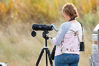 Equipped with a spotting scope, camera, binoculars and cellphone, a visitor enjoys the wildlife watching at Slippery Ann Elk Viewing Area.