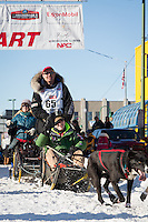 Ken Anderson and team leave the ceremonial start line at 4th Avenue and D street in downtown Anchorage during the 2014 Iditarod race.<br /> Photo by Jim R. Kohl/IditarodPhotos.com