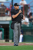 Home plate umpire Adrian Gonzalez signals one warm up pitch left during a game between the Lansing Lugnuts and the Burlington Bees at Community Field on July 28, 2014 in Burlington, Iowa. The Lugnuts won 9-2.   (Dennis Hubbard/Four Seam Images)