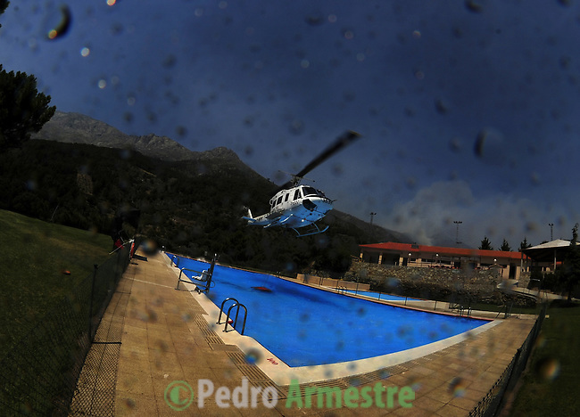 SPAIN, EL ARENAL : A firefighters' helicopter lifts water from a swimming pool in El Arenal, near Avila as forest fires raged in the region, on July 29, 2009. Spain lost 155,000 hectares to fire in 2005 and another 188,000 hectares in 2006 but was spared major wildfire damage in the past two years, the exception being the Canary Islands in the Atlantic which suffered major blazes in 2007.  on July 29, 2009. (C) Pedro ARMESTRE
