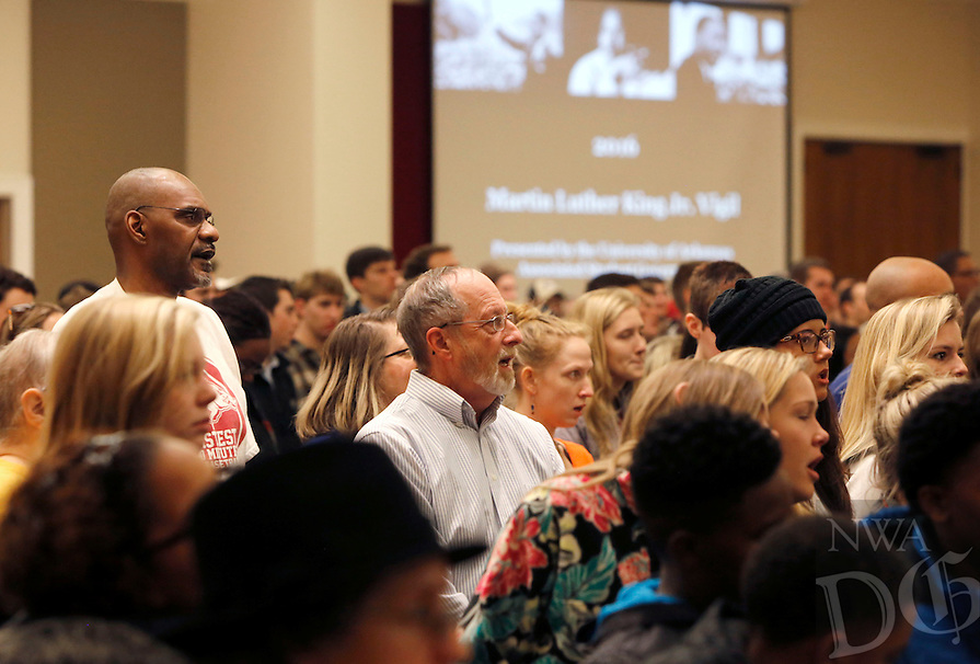 NWA Democrat-Gazette/DAVID GOTTSCHALK  Mayor Lioneld Jordan (center), participates in songs and chants Monday, January 18, 2016, led by Sandra Walton, a junior at the University of Arkansas, at the University of Arkansas in Fayetteville. The songs and chants were part of the Martin Luther King, Jr. Vigil and Freedom March celebration co-sponsored by the University of Arkansas Associated Student Government, the Black Student Association and the Northwest Arkansas Martin Luther King, Jr. Council.