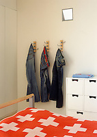 Three pairs of jeans hanging from hooks on the bedroom wall create a 'living' sculpture