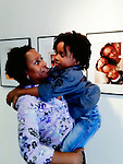 Mother holding her child, a young boy, at Long Island Center of Photography's Family Portrait Day gallery reception at African American Museum, Hempstead, New York, USA, on October 16, 2011.