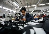 Workers make backpacks at the XinXin Bag Factory in Shanghai, China..
