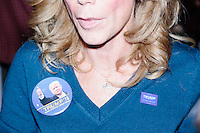 Trump campaign volunteer Catherine Leafe of Manchester, New Hampshire, wears two Trump campaign buttons and a cross as she speaks with reporters before Republican presidential candidate and real estate mogul Donald Trump speaks at a meeting of the New England Police Benevolent Association executive council at the Sheraton Portsmouth Harborside Hotel in Portsmouth, New Hampshire, USA. At the gathering, the group endorsed Trump for president. A small group of perhaps 20 Trump supporters stood outside the hotel and there was a larger group of anti-Trump protesters, mostly across the street. One of the protest organizers estimated that there were around 230 protesters gathered.Many protesters expressed disagreement with Trump's recent statements that he would ban all Muslims from entering the country. Trump brought up the recent shooting in San Berdardino, Calif., at the meeting.