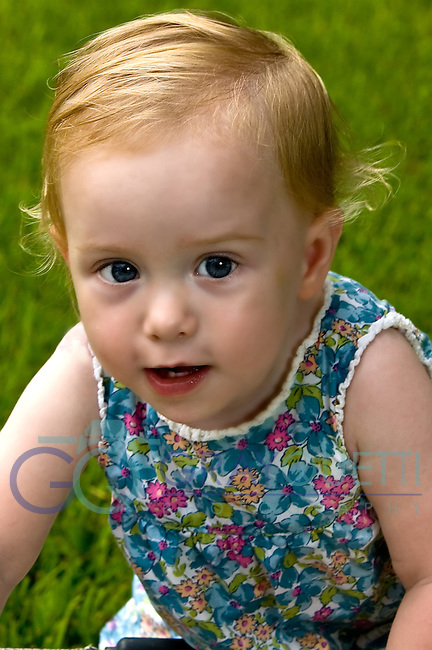 Portrait of baby, age 16 months, with reddish/blonde hair, blue eyes, wearing a colorful flower patterned shirt.