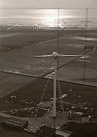 Growian: EUROPA, DEUTSCHLAND, SCHLESWIG- HOLSTEIN,  (GERMANY), 27.10.1988:   Deutschland, Schleswig-Holstein, Kaiser-Wilhelm-Koog, Versuchs- und Demonstrationsanlage GROWIAN, Grosse-Windeenergie-Anlage. Abbruch der Anlage nach dem Scheitern der Technik. Die Anlage war auf Grund von unerwuenschten Schwingungen stillgelegt worden. GROWIAN mit Messanlagen im Versuchsfeld, Die GROWIAN  war eine oeffentlich gefoerderte Windkraftanlage, die zur Technologieerprobung in den 1980er Jahren im Kaiser-Wilhelm-Koog bei Marne errichtet wurde. Es handelte sich um einen zweiflügligen Leelaeufer  mit einer Nabenhoehe von etwa 100 Metern...GROWIAN war lange Zeit die groesste Windkraftanlage der Welt. Vieles an der Anlage war neu und in dieser Groessenordnung noch nicht erprobt. Da es bei der Gehaeuseauslegung zu einem Fehler kam, konnte die Anlage nicht bei voller Leistung betrieben werden. Die Probleme mit Werkstoffen und Konstruktion ermoeglichten keinen kontinuierlichen Testbetrieb. Die meiste Zeit zwischen dem ersten Probelauf am 6. Juli 1983 bis zum Betriebsende im August 1987 stand die Anlage still. Offizieller Betriebsbeginn war am 4. Oktober 1983. Der offizielle Startschuss des Probebetriebs wurde am 17. Oktober 1983 bei einer feierlichen Eroeffnung gegeben. .. Luftbild, Luftaufnahme, Luftansicht, Aufwind-Luftbilder,  .c o p y r i g h t : A U F W I N D - L U F T B I L D E R . de.G e r t r u d - B a e u m e r - S t i e g 1 0 2, 2 1 0 3 5 H a m b u r g , G e r m a n y P h o n e + 4 9 (0) 1 7 1 - 6 8 6 6 0 6 9 E m a i l H w e i 1 @ a o l . c o m w w w . a u f w i n d - l u f t b i l d e r . d e.K o n t o : P o s t b a n k H a m b u r g .B l z : 2 0 0 1 0 0 2 0  K o n t o : 5 8 3 6 5 7 2 0 9.V e r o e f f e n t l i c h u n g n u r m i t H o n o r a r n a c h M F M, N a m e n s n e n n u n g u n d B e l e g e x e m p l a r !.
