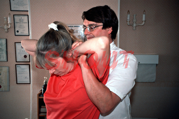 Osteopath performing thoracic manipulation, lift, on a patient. This image may only be used to portray the subject in a positive manner..©shoutpictures.com..john@shoutpictures.com