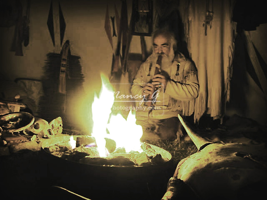 A Native American Indian reenactor playing the flute in his tipi
