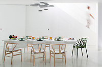 The open plan dining area features chairs by Hans Wegner and a ceiling light of mercury glass