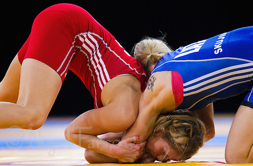 11 DEC 2011 - LONDON, GBR - Aline Focten (GER) (in red) tries to break free from Laura Skujina's (LAT) (in blue) hold during their women's 63kg category bronze medal bout during the London International Wrestling Invitational and 2012 Olympic Games test event  at the ExCel Exhibition Centre in London, Great Britain .(PHOTO (C) NIGEL FARROW)