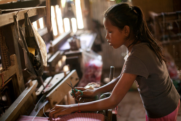 A young girl works in a village textile factory outside of Phnom Penh, Cambodia. <br /> <br /> Photos &copy; Dennis Drenner 2013.
