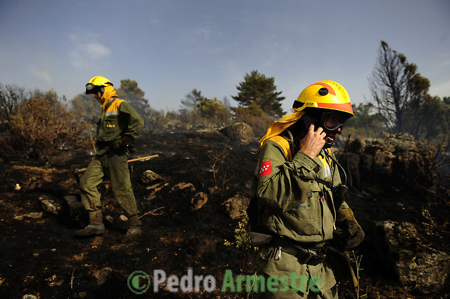 Members of the fire brigade walk around the area where a fire burns in the Cerro del Castillo hill near the town of Collado Mediado, northeast of Madrid, which forced the evacuation of some 2,000 people, the mayor of the town, Maria Rubio, told news radio Cadena Ser. Four firefighters were killed and two were seriosuly injured Tuesday as they battled another wildfire in a natural park in northeastern Spain, a spokeswoman for the local government said. on July 21, 2009. (C) Pedro ARMESTRE