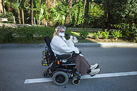 "Switzerland. Canton Ticino. Lugano. An elderly woman seated on a motorised wheelchair rides on the road with a dog on her knees. The aged woman wears a mask on the face to protect herself from the Coronavirus (also called Covid-19. Due to the spread of the coronavirus, the Federal Council has categorised the situation in the country as ""extraordinary"". It has issued a recommendation to all citizens to stay at home, especially the sick and the elderly. The Federal Council (German: Bundesrat, French: Conseil fédéral, Italian: Consiglio federale, Romansh: Cussegl federal) is the seven-member executive council that constitutes the federal government of the Swiss Confederation. From March 16 the government ramped up its response to the widening pandemic, ordering the closure of bars, restaurants, sports facilities and cultural spaces. Only businesses providing essential goods to the population – such as grocery stores, bakeries and pharmacies – are to remain open. 19.03.2020 © 2020 Didier Ruef"