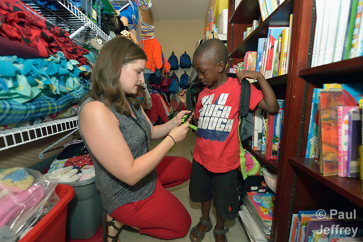 Christine Baer, a congregational resource developer with Church World Service in Lancaster, Pennsylvania, helps David Kalamba, a 6-year old resettled refugee from the Democratic Republic of the Congo, adjust a backpack in the agency's supply room. Church World Service resettles refugees in Pennsylvania and other locations in the United States. <br /> <br /> Photo by Paul Jeffrey for Church World Service.