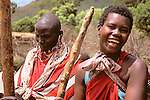 Africa, Kenya, Maasai Mara. Two Maasai women enjoy demonstrating the building of a home (traditionally built by the women) in their boma at Olanana in the Maasai Mara.
