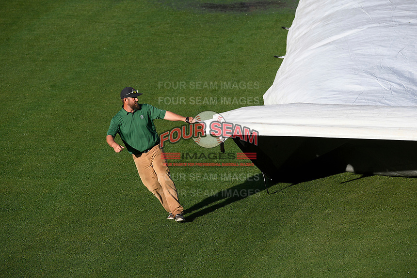 After the weather cleared, head groundskeeper Greg Burgess, along with his Greenville Drive turf crew, pulled the tarp off the field in advance of a game on Friday, April 19, 2019, at Fluor Field at the West End in Greenville, South Carolina. Greenville won, 2-0. (Tom Priddy/Four Seam Images)