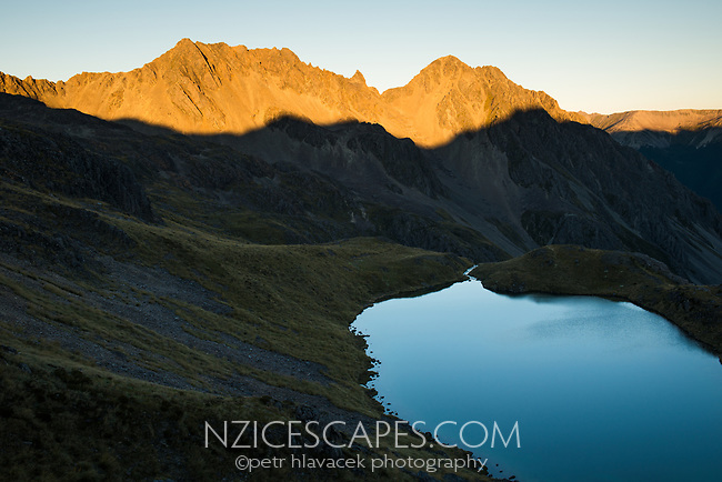 Sunset on St. Arnaud Ranges with pristine Hinapouri Tarn, Nelson Lake National Park, South Island, New Zealand, NZ