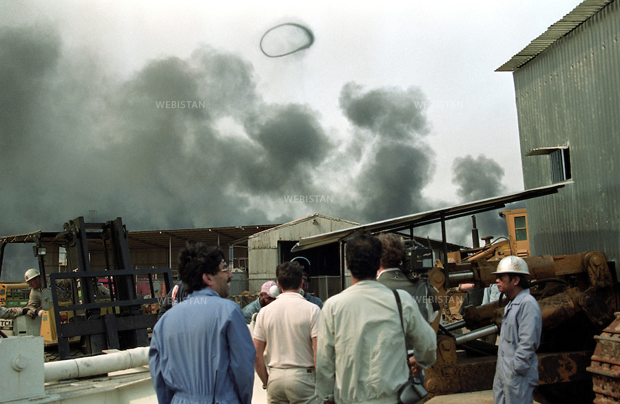 A smoke ring from a burning oil well soars over the camp of fire fighters. ..Kuwait was invaded by Iraqi President Saddam Hussein on August 2, 1990, claiming the oil-rich Kuwait as Iraqi territory. The small state of Kuwait owns almost 10% of the worldÕs oil reserves. After annexation, its monarchy was removed, and a new Kuwaiti governor was installed by Saddam Hussein...Approved by the UN Security Council, an American-led coalition fought the Gulf War to reinstall the Kuwaiti Emir. After 6 weeks of war in January/February 1991, Iraq was forced to retreat its troops from Kuwait. During withdrawal, the Iraqi army practiced a scorched earth policy by placing land mines and setting fire to Kuwaiti oil wells. More than 500 oil wells were burning in Kuwait. The inferno took over nine months to extinguish; the costs to restore the Kuwaiti petrol infrastructure exceeded 5 billion US dollar.