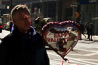 New York, United States. 14th February 2013 -- A man carries a globe as a present during celebrations of Saint Valentine's day in New York. Photo by Eduardo Munoz Alvarez / VIEWpress.