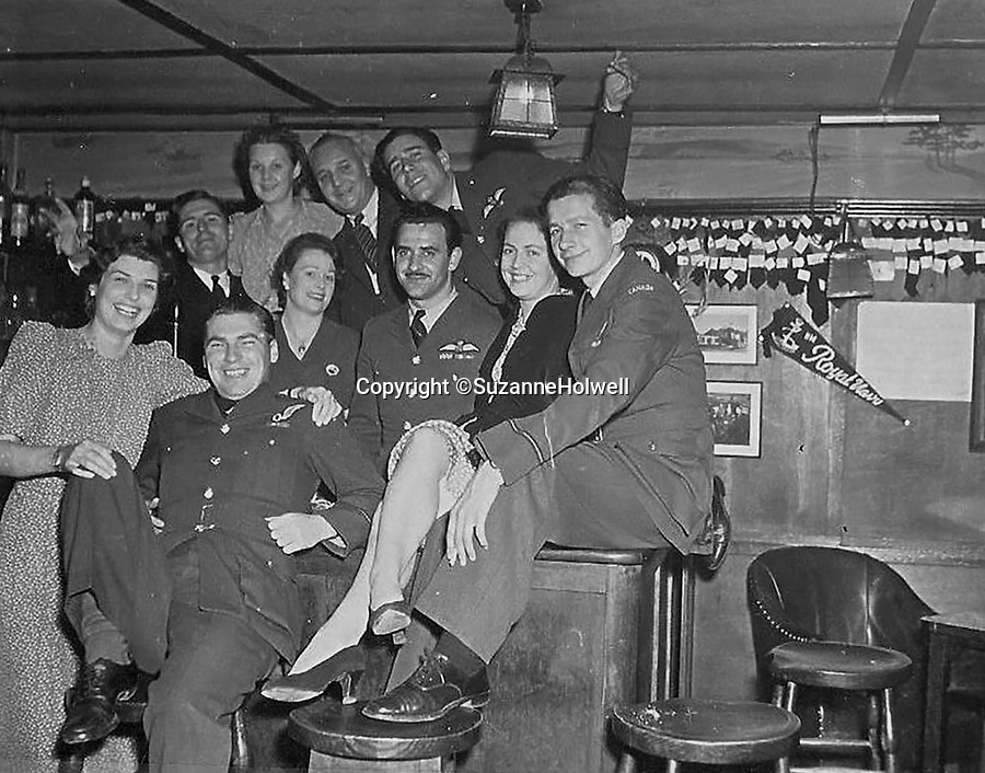 BNPS.co.uk (01202 558833)<br /> Pic: SuzanneHolwell/BNPS<br /> <br /> Flight crew at the pub and, rear, sections of their ties which were snipped off and pinned to the wall by barmaid Ailsa Lobb. <br /> <br /> Sections of a torn-down pub ceiling which are covered in 250 signatures from World War Two heroes have been salvaged and turned into a memorial.<br /> <br /> The merry airmen left their mark during raucous evenings at the George and Dragon in the village of Clyst St George in Devon.<br /> <br /> Many of the brave men who signed or drew on the wood ceiling perished in the war in the skies with the Luftwaffe.<br /> <br /> One of them, Sergeant Albert Stilin, of 257 Squadron, was killed aged 21 when he crashed his Hurricane into this pub's roof on September 30, 1942. Another airman later put the initials 'RIP' put after his name.<br /> <br /> The ceiling was taken down in 1975 and half of it was destroyed. <br /> <br /> Robin and Suzannah Holwell recovered the surviving planks from a RAFA association store room in 2009 and have carried out a decade-long preservation project, putting the sections in frames and researching the men behind signatures.