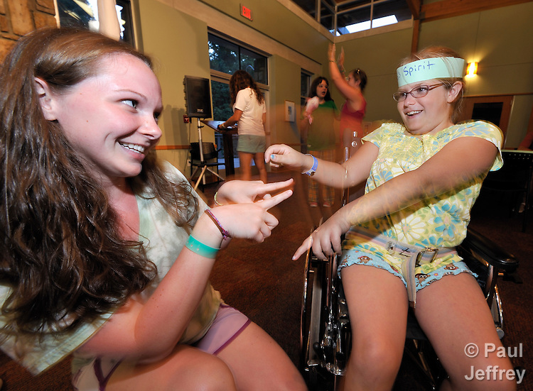 Counselor Kelly Allison (left) dances with camper Sydney Roberts during an evening party at Camp Aldersgate in Little Rock, Arkansas. The camp, supported by United Methodist Women, offers children suffering from a variety of disabilities a safe and fun experience similar to that which normally-abled children often enjoy.