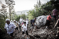 Pilgrims climb the Mt. Krizevac between the 15 stations of the  Via Crucis. Some of them walks barefoot. It takes 3 hours to climb through the steep and bumpy path.  The temperature hits 41&deg;C. <br /> Medjugorje, Bosnia and Herzegovina. July 2012