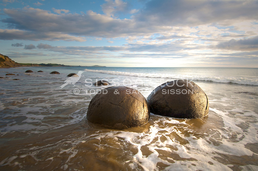 Moeraki Boulders image | round rocks in sea | golden sun | waves around boulders | Coastal Otago New Zealand