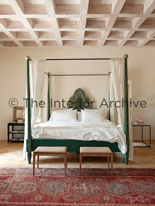 Reclaimed wood and natural Majorcan stone is used throughout the house. The bedroom is simply furnished with a green painted double four-poster bed,  and red patterned rugs on the tiled floor.