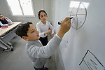 Students write on the whiteboard in a class at the Al Bishara School, which is run by the Dominican Sisters of St. Catherine of Siena in Ankawa, near Erbil, Iraq. The students and the Dominican Sisters themselves were displaced by ISIS in 2014. The nuns have established schools and other ministries among the displaced.