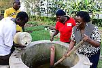 KENYA, County Kakamega, Bukura, village Eshibeye, milk cow farm, the dung is used in the biogas plant / KENIA, County Kakamega, Bukura, Dorf Eshibeye, Milchkuh Farm, Kuhdung wird in der Biogasanlage verwendet, rechts  Milchbaeuerin Fanice Khanali, 67 Jahre, rotes T-shirt GIZ Mitarbeiterin Flora Ajwera