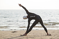 27 JUL 2013 - CROMER, GBR - A competitor stretches ahead of the start of The Anglian Triathlon 2013 at West Runton, North Norfolk, Great Britain (PHOTO COPYRIGHT © 2013 NIGEL FARROW, ALL RIGHTS RESERVED)