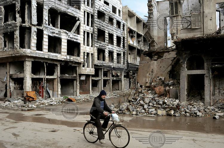 A man cycles past ruined buildings in a battle damaged street. After a three year long battle and siege by government troops, armed opposition fighters left the old centre of Homs, the only part they still occupied, in May 2014. Much of the city has been reduced to ruins by the fighting.