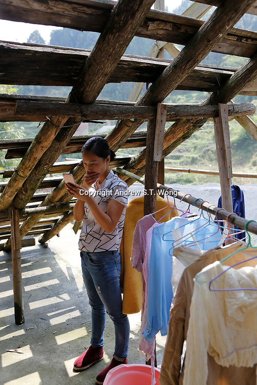 A woman of the ethnic Bouyei Tribe checks her mobile phone after hanging up laundry at home at Wangmo County in China's southwestern Guizhou Province, April 2019.