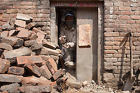 A man removes rubble from his destroyed house. Shanku, near Kathmandu, Nepal. May 9, 2015