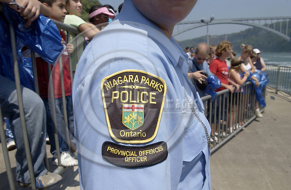 Niagara Falls, Ontario, Canada - 01 August 2006---Emblem on the upper arm of a provincial offences officer of the Niagara Parks Police, supervising tourists / visitors  lining up for a cruise on the Niagara River---people, tourism---Photo: Horst Wagner / eup-images