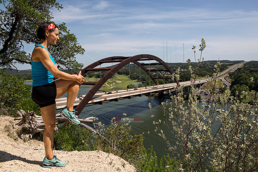 A cross country runner stretches on top of the 360 Bridge while enjoying the beautiful view of Lake Austin, Texas.