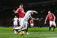 Angel Rangel of Swansea City goes over from a challenge by Matteo Darmian of Manchester United and was booked for an alleged dive during the Barclays Premier League match between Manchester United and Swansea City played at Old Trafford, Manchester on January 2nd 2016