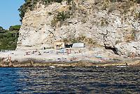 Sunbathers enjoy a rugged rock beach along the Sorrento coast, Compania, Italy