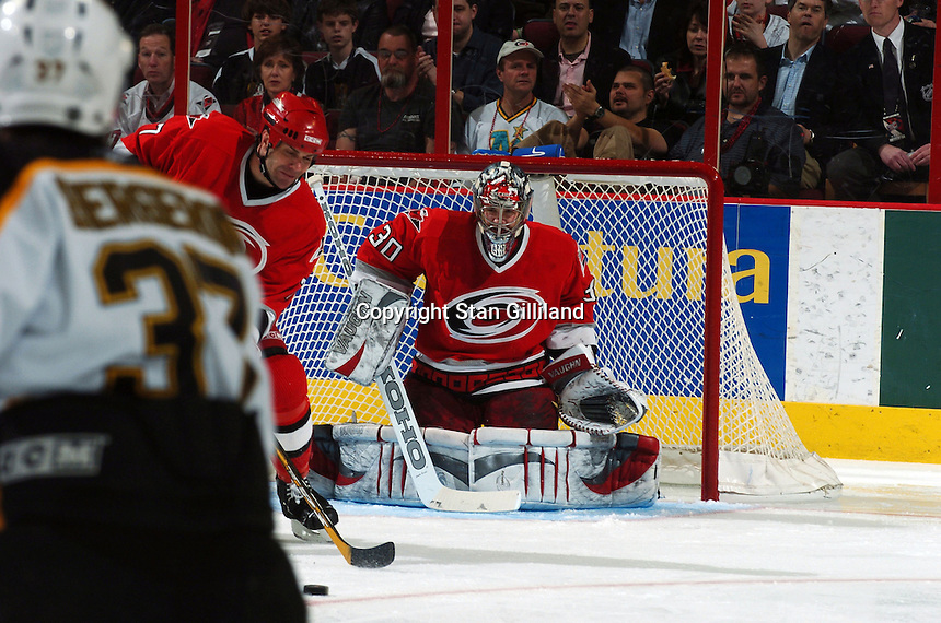 Carolina Hurricanes' Niclas Wallin, left, of Sweden attempts to clear the puck in front of teammate and goaltender Cam Ward during a game with the Boston Bruins at the RBC Center in Raleigh, NC Wednesday, March 1, 2006. The Hurricanes won 4-3...