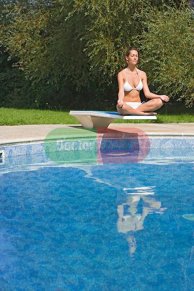young woman in bikini sits yoga style on board above pool