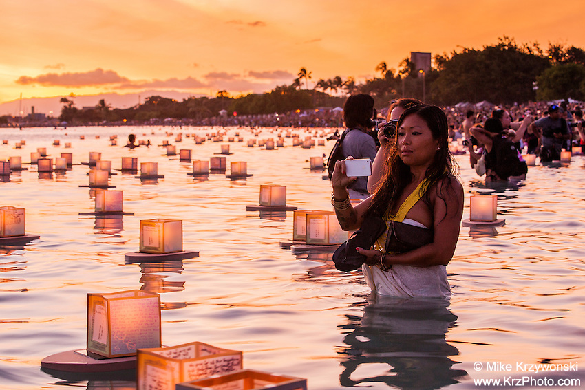 Asian woman photographing lanterns floating in the water during the 15th Annual Lantern Floating Ceremony at Ala Moana Beach Park in Honolulu on Memorial Day