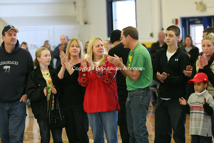 TORRINGTON, CT - 13 December, 2008 - 121308MO06 - Liz Garrity, in red, is comforted by her husband Mike Garrity (in green) at the Torrington Armory Saturday as the scoreboard  dedicated to the memory of Liz Garrity's late son, Dustin Arigoni, who was murdered in December 2006, is revealed. Jim Moore Republican-American.