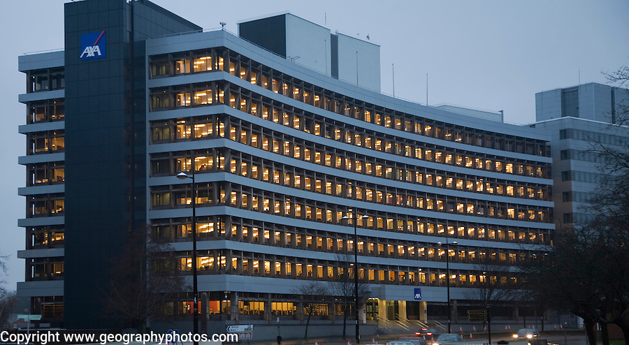 AXA insurance office illuminated by electric lights in winter afternoon, Ipswich, Suffolk, England