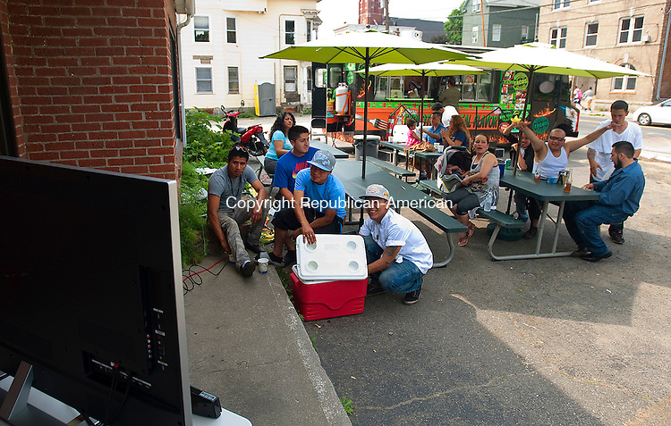 WATERBURY, CT-061714JS04--Soccer fans gather around a big screen television at the site for Los Garcia Mexican food truck on East Main Street in Waterbury on Tuesday as they watch the FIFA Word Cup game between Mexico and Brazil.<br /> Park Jim Shannon Republican-American