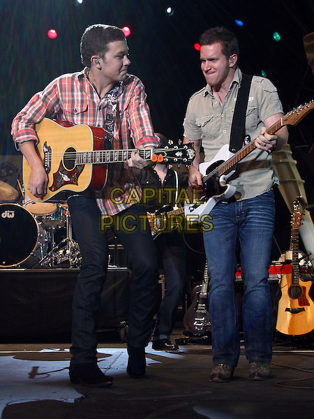 Scotty McCreery performs at 2012 ACM Weekend on Fremont Street Expereince, Las Vegas, Nevada, USA, .30th March 2012..music concert gig live on stage full length  red tartan plaid checked shirt playing  guitar .CAP/ADM/MJT.© MJT/AdMedia/Capital Pictures.