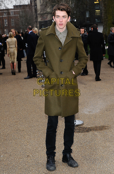 DOUGLAS BOOTH.The Burberry Prorsum Fashion Show during London Fashion Week Autumn/Winter 2011, Kensington Gardens, London, England..21st February 2011.LFW full length green coat hands in pockets black jeans  .CAP/CJ.©Chris Joseph/Capital Pictures.